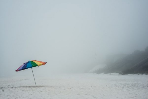 """Under The Rainbow"" by photographer Aranka Israni captures a lone rainbow colored umbrella in the sand at Alys Beach, Florida. Full color, limited edition print."